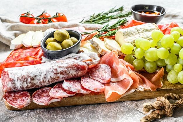 Włoska antipasto, drewniana deska do krojenia z szynką parmeńską, szynką, parmą, kozim serem camembert, oliwkami, winogronami. antipasti. szara powierzchnia. widok z góry