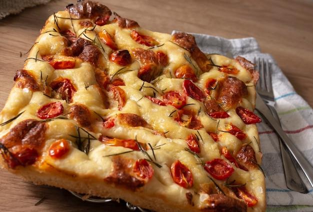Włoska focaccia pugliese z rozmarynem i oliwą z oliwek i pomidorami na drewnianym stole