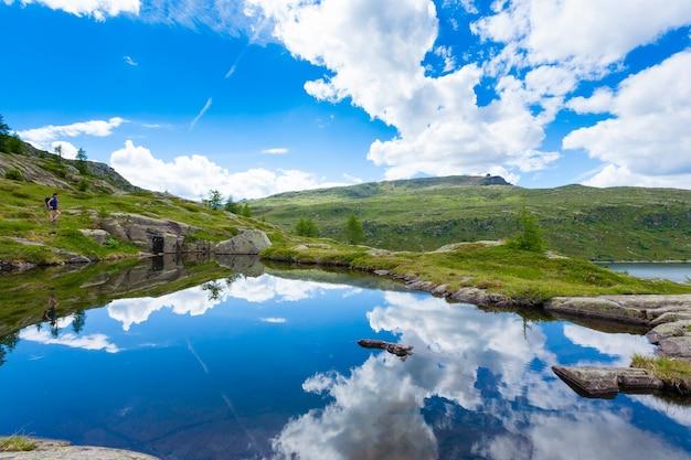 Włoska panorama górska, chmury nad jeziorem alpejskim. trekking w pobliżu passo san pellegrino we włoskich alpach. sport i outdoor