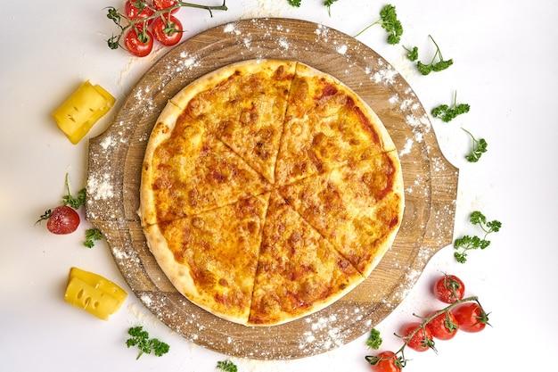 Włoska pizza margarita z mozzarellą i sosem pomidorowym na drewnianym stole, pomidory i ser na tle