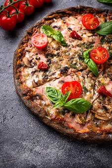 Włoska pizza na czarnym cieście. modne jedzenie