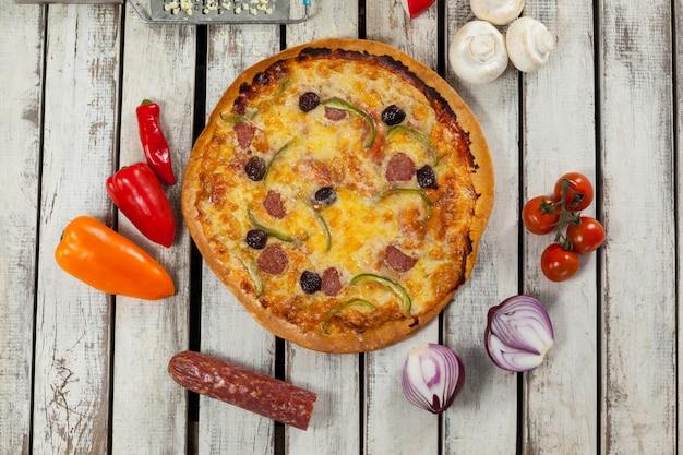Włoska pizza na drewnianej desce z warzywami i przyprawami