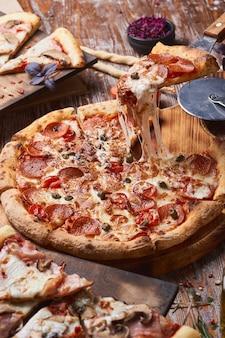 Włoska pizza na drewnianym stole. kawałek gorącej pizzy z rozciągającym się serem.