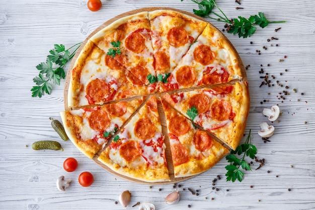 Włoska pizza pepperoni na jasnym drewnianym