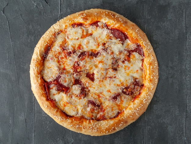 Włoska pizza pepperoni. z kiełbasą pepperoni, sosem pomidorowym, serem mozzarella, sulguni i parmezanem. szeroki bok. widok z góry. na szarym tle betonu. odosobniony.