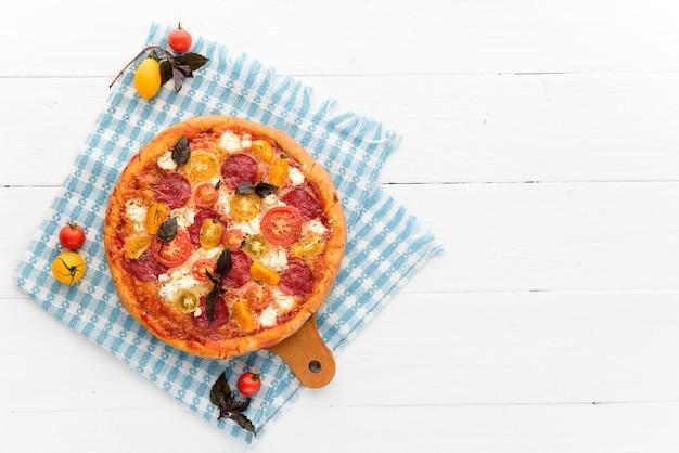 Włoska pizza pepperoni z salami i serem na rustykalnym drewnianym białym tle