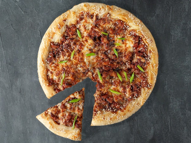 Włoska pizza. wędzony kurczak, ser mozzarella, sulguni, sos pomidorowy, przyprawy i szczypiorek. kawałek jest odcięty od pizzy. widok z góry. na szarym tle betonu. odosobniony.