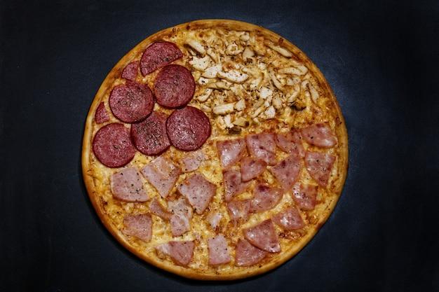 Włoska pizza z czterema rodzajami mięsa na drewnianym czarnym tle widok z góry smaczna i apetyczna