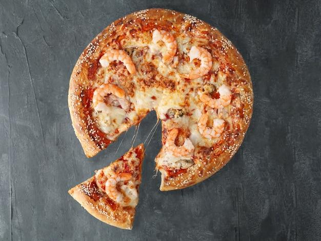 Włoska pizza. z krewetkami tygrysimi, kalmarami, małżami, sosem pomidorowym, serem mozzarella. kawałek jest odcięty od pizzy. widok z góry. na szarym tle betonu. odosobniony.