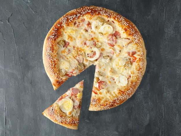 Włoska pizza. z kurczakiem, kiełbaskami, jajkiem na twardo, ogórkami kiszonymi, pomidorem, sosem pomidorowym, serem mozzarella. kawałek jest odcięty od pizzy. widok z góry. na szarym tle betonu. odosobniony.