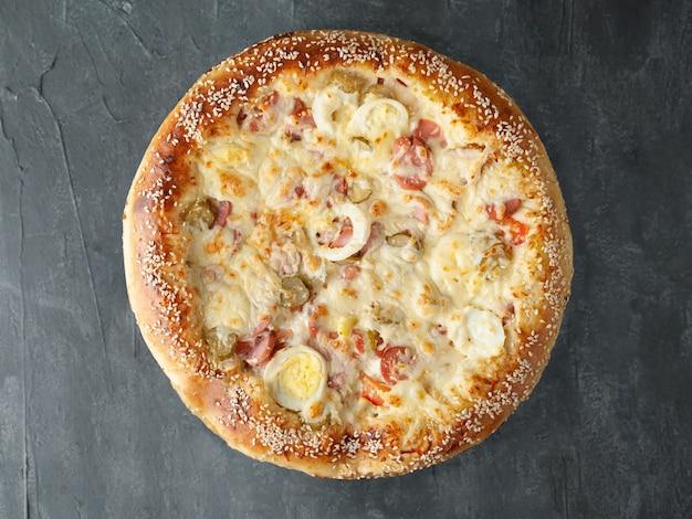 Włoska pizza. z kurczakiem, kiełbaskami, jajkiem na twardo, ogórkami kiszonymi, pomidorem, sosem pomidorowym, serem mozzarella. szeroki bok. widok z góry. na szarym tle betonu. odosobniony.