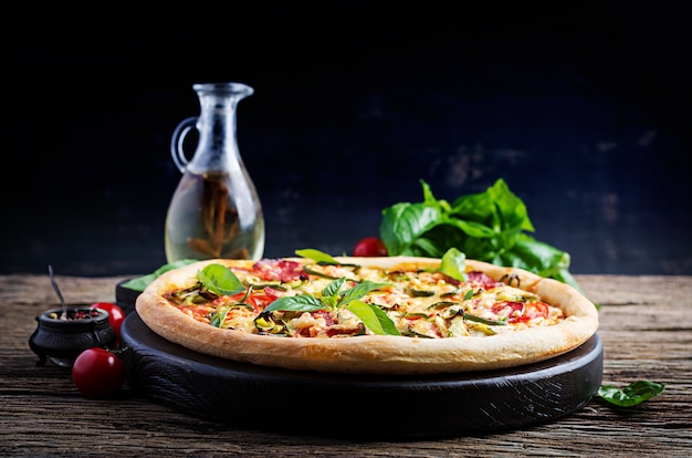 Włoska pizza z kurczakiem, salami, cukinią, pomidorami i ziołami na rocznika drewnianym tle. kuchnia włoska
