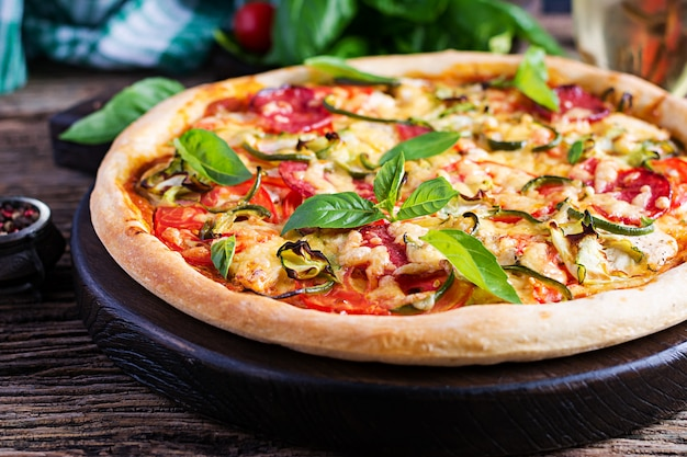 Włoska pizza z kurczakiem, salami, cukinią, pomidorami i ziołami