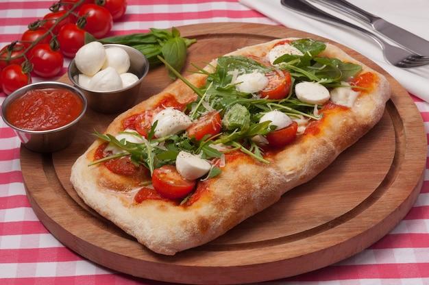 Włoska pizza z mozzarellą, pomidorami i rukolą