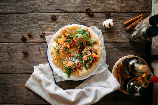 Włoska pizza z oliwkami łososia i rukolą