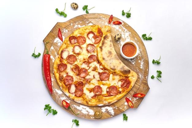 Włoska pizza z pepperoni, mozzarellą i sosem pomidorowym drewniany stół na tle papryczki chili