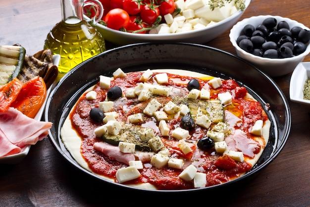 Włoska pizza z pomidorami, mozzarellą, czarnymi oliwkami i listkami bazylii