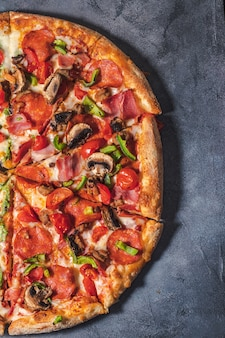 Włoska pizza z pomidorem, pieczarkami, boczkiem, łososiem i papryką. dostawa jedzenia na czarnym tle