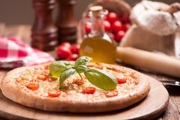 Włoska pizza z pomidorem polana roztopionym złotym serem, ziołami i bazylią podawana na okrągłej drewnianej desce na starym drewnianym stole