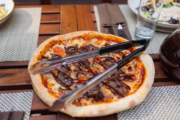 Włoska pizza z prosciutto pomidorkami oliwkami oliwą parmezanem i rukolą. strzał studio niewyraźne kolorowe tło.