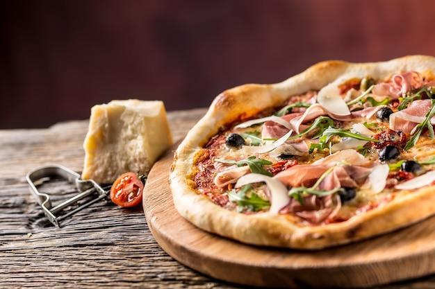 Włoska pizza z prosciutto pomidorkami oliwkami oliwą parmezanem i rukolą