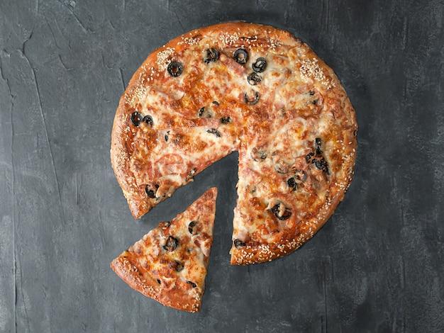 Włoska pizza. z szynką, cervelat, węglanem, boczkiem, pomidorami, oliwkami, sosem pomidorowym, serem mozzarella. kawałek jest odcięty od pizzy. widok z góry. na szarym tle betonu. odosobniony.