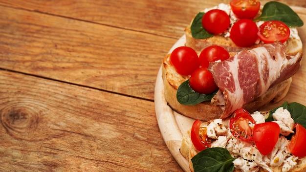 Włoska przystawka. bruschetta na desce na drewnianym tle rustykalnym. pyszna świeża przystawka z pomidorami i boczkiem