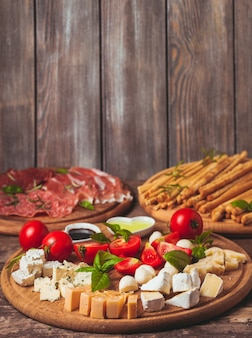 Włoska przystawka - różne rodzaje szynki, sera i grissini z miejscem na kopię na ścianie
