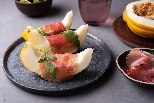 Włoska przystawka z prosciutto i melona, szynka z melonem na talerzu na szarym tle betonu.