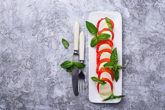 Włoska sałatka caprese z mozzarellą, pomidorami i bazylią. widok z góry