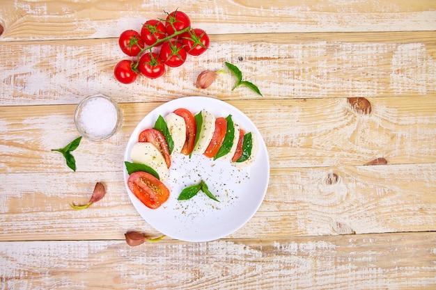 Włoska sałatka caprese z plasterkami pomidorów, mozzarellą, bazylią, oliwą z oliwek.