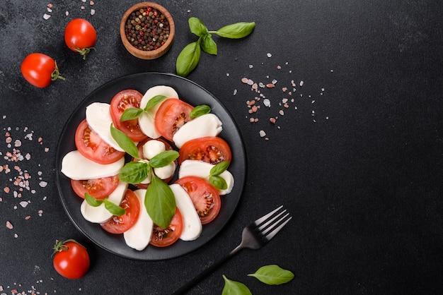 Włoska sałatka caprese z plastrami pomidorów, serem mozzarella, bazylią, oliwą z oliwek. podawane w vintage czarnej płycie na ciemnym betonowym tle