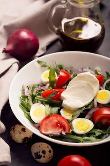 Włoska sałatka przygotowywana z rukoli, mozzarelli, jajek. czarne tło