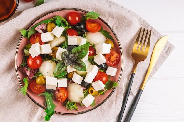 Włoska sałatka z fetą, oliwkami, pomidorami, rukolą i melonem