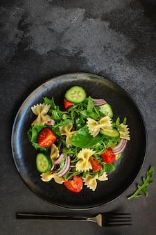 Włoska sałatka z makaronem farfalle, warzywa, mieszać liście, widok z góry