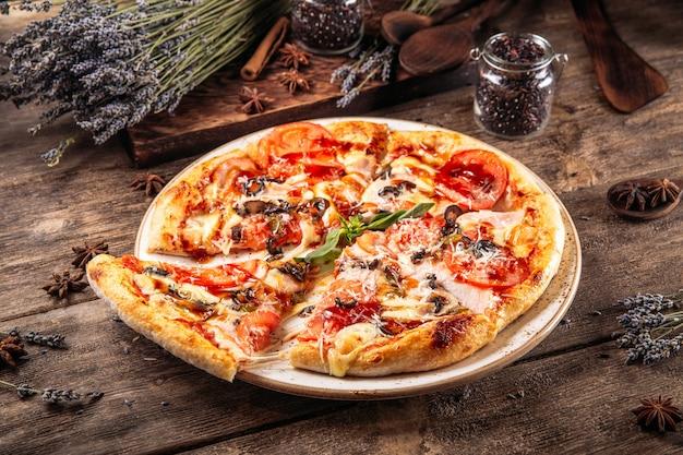 Włoska świeżo upieczona puszysta pizza z oliwkami i pomidorami na drewnianym stole