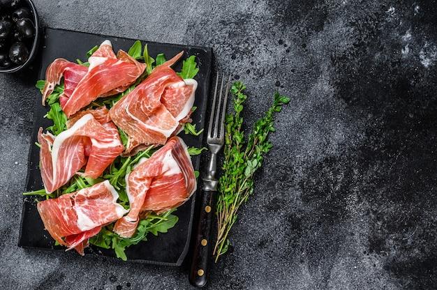 Włoska szynka parma prosciutto crudo suszona na marmurowej desce. czarny stół. widok z góry. skopiuj miejsce.