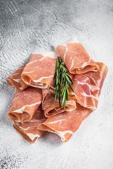 Włoska szynka parmeńska prosciutto crudo na stole. biały stół. widok z góry.