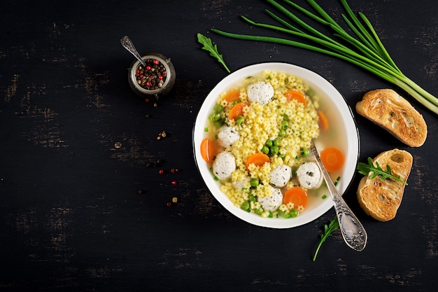 Włoska zupa z klopsika i bezglutenowy makaron stelline w misce na czarnym stole.