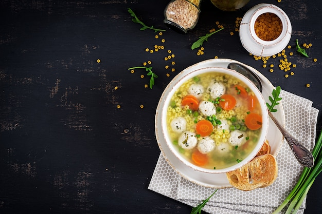Włoska zupa z klopsika i makaron stelline w misce na czarnym stole.