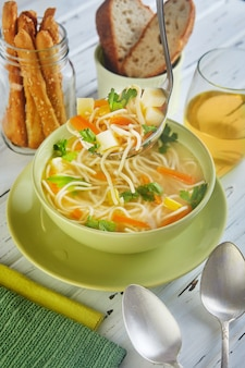 Włoska zupa ze spaghetti w zielonym talerzu, na stole z serwetkami i drinkiem w szklance