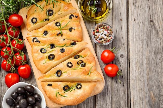 Włoski chleb focaccia z oliwkami i rozmarynem na rustykalnym drewnianym stole.