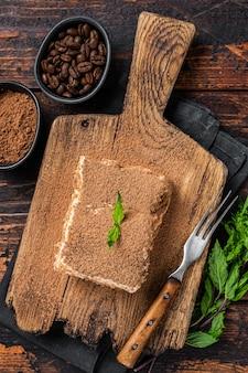 Włoski deser ciasto tiramisu z kakao i miętą na drewnianej desce. ciemne drewniane tło. widok z góry.
