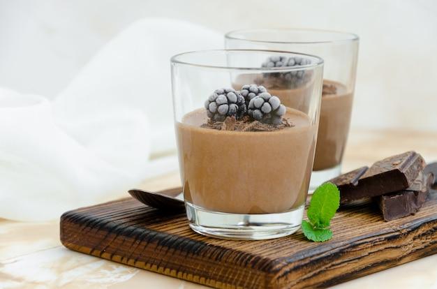 Włoski deser. czekoladowe pana cotta, mus, krem lub budyń z jeżyną w szklance na desce na jasnym tle betonowym. orientacja pozioma.