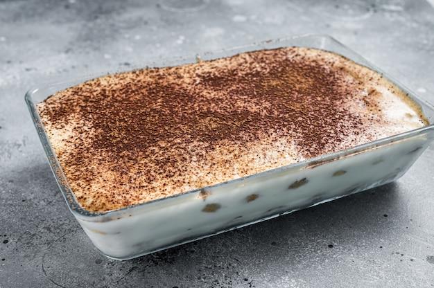 Włoski deser tiramisu polany kakao. szare tło. widok z góry.
