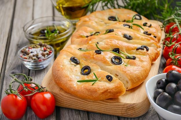 Włoski focaccia chleb z oliwkami i rozmarynem na nieociosanym drewnianym tle.