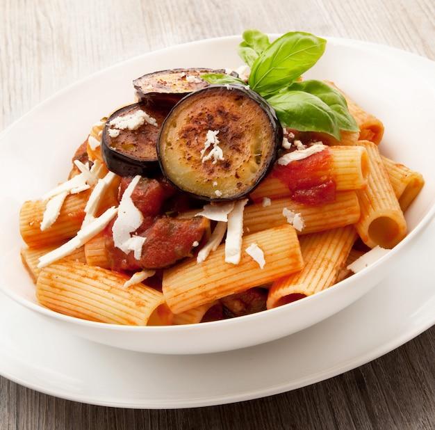 Włoski makaron alla norma na drewnianym stole