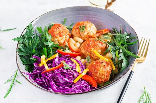 Włoski makaron. cavatappi z klopsikami i surówką. obiad. koncepcja slow food