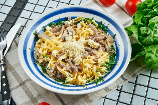 Włoski makaron fettuccine w sosie serowym z parmezanem, cielęciną, ziołami w białej ceramicznej misce na białym stole. smaczny stolik