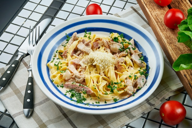 Włoski makaron fettuccine w sosie serowym z parmezanem, kurczakiem i szynką, zioła w białej ceramicznej misce na białym stole. smaczny stolik